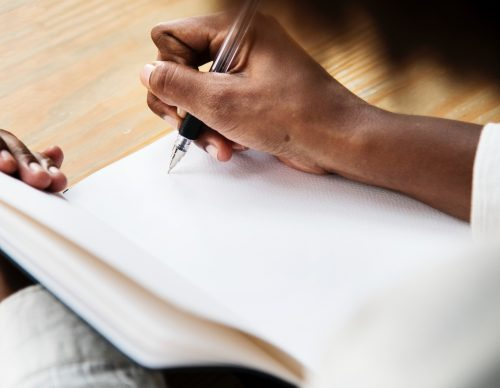 A person starts writing on a blank page in a journal. Writing in a journal helps find the meaning in a confusing tarot spread. This is one of ten solutions I share for when you can't read tarot for yourself.