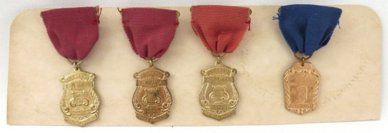 three red and one blue music festival medals